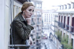 Lost and sad woman at home balcony suffering depression looking thoughtful and solitary. In female depression concept and sadness emotion dramatic facial royalty free stock images