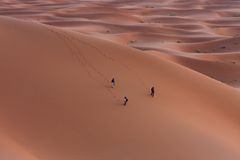 Lost in sands. My friends walking through the desert Stock Image
