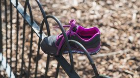 Lost shoe. oncept of loneliness. Funny moment of childrens gray and purple shoe got stuck in the fence Royalty Free Stock Images