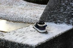 A lost shoe on snow. Some one left a shoe on a wall on a snowy day royalty free stock images