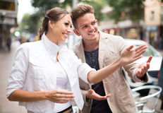 Lost smiling woman asking stranger at the street stock photos