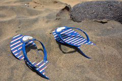 Lost striped flip-flops on the beach. Lost striped flip-flops on the black sand beach Stock Photography