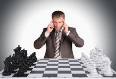 Lost in thought businessman and chess board Stock Image
