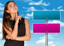 Lost in thought businesswoman. Crossroads road sign as backdrop Royalty Free Stock Photos