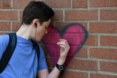 Lost in thought. Teenage boy standing at a wall touches a graffiti heart lost in thought stock image