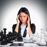 Lost in thought woman looking at chess board Stock Images