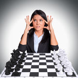 Lost in thought woman looking up. Chessboard with Royalty Free Stock Photos
