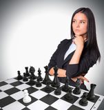 Lost in thought woman looking up. Chessboard with Stock Images