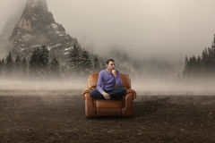 Lost in thoughts. Challenge. Casual business man in armchair lost on a foggy field with dark atmosphere behind Royalty Free Stock Photo