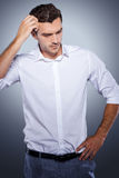 Lost in thoughts. Handsome young man in white shirt holding hand in hair and looking away while standing against grey background Stock Photography