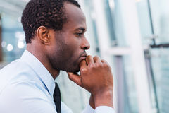 Lost in thoughts. Side view of thoughtful young African man in shirt and tie holding hands on chin and looking away Stock Photography