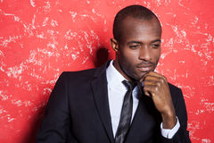 Lost in thoughts. Thoughtful young African man in formalwear holding hand on chin and looking away while sitting against red background Stock Photography