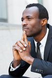 Lost in thoughts. Thoughtful young African man in formalwear keeping hands clasped and looking away while sitting outdoors Stock Image