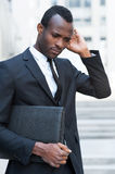 Lost in thoughts. Thoughtful young African man in formalwear keeping hands clasped and looking away while sitting outdoors Stock Photography