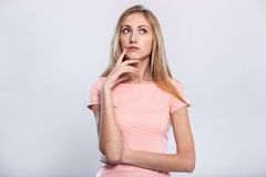 Lost in thoughts. Thoughtful young blond hair woman holding hand on chin and looking away while standing against grey background Stock Photo
