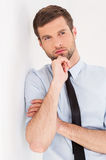 Lost in thoughts. Thoughtful young man in shirt and tie looking away and holding hand on chin while leaning at the wall Royalty Free Stock Photo