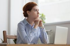 Lost in thoughts woman sits at workplace desk in office. In front of laptop holds hands on chin looking away thinking about working moments. Businesswoman royalty free stock images