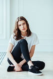 Lost in thoughts. Young beautiful brunette hipster woman sitting on floor near huge window and looking away Royalty Free Stock Photos