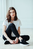 Lost in thoughts. Young beautiful brunette hipster woman sitting on floor near huge window and looking away Royalty Free Stock Photography