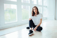 Lost in thoughts. Young beautiful brunette hipster woman sitting on floor near huge window and looking away Stock Photos