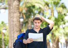 Lost tourist with bag holding map. Portrait of a lost tourist with bag holding map Royalty Free Stock Photos