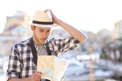 Lost tourist consulting guide in a coast town. Lost tourist consulting a confusing guide in a coast town street on vacation royalty free stock images