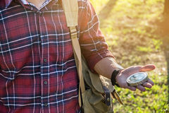 A lost tourist in a hike with compass aiming the direction in th Stock Photo