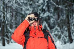 A lost tourist man in a winter forest. With binoculars Royalty Free Stock Image