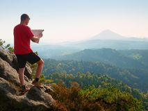 Lost tourist  on peak looking into landscape  while check paper map, hiking  in nature. Lost tourist  on the rocky peak looking into landscape  while check the Stock Image
