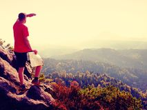 Lost tourist  on peak looking into landscape  while check paper map, hiking  in nature. Lost tourist  on the rocky peak looking into landscape  while check the Royalty Free Stock Image