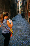 A lost tourist in Rome. A lost tourist is looking in her map, trying to find her way in a deserted alley in rome Stock Image