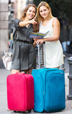 Lost tourists  looking for hotel. Positive lost girl tourists with suitcases looking for hotel Stock Photos