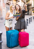 Lost tourists  looking for hotel. Positive lost tourists with suitcases and map looking for hotel Royalty Free Stock Photo