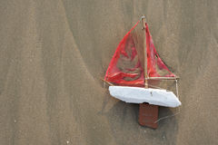 Lost toy boat washed up on beach from above Stock Images