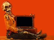 Lost treasure. Malicious skeleton with an empty chest on red background Royalty Free Stock Photo