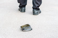 Lost wallet on the street and legs of the walking man Stock Photo