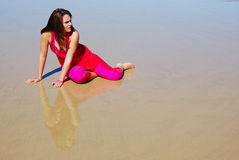 Lost woman. A beautiful lost young Caucasian white woman in pink wet clothes sitting in the sand on the beach with a helpless expression in her face Royalty Free Stock Photography
