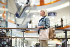 Lost woman in big shopping mall. Serious lost mature woman with blond hair standing in big shopping mall and looking around while choosing clothing stores for royalty free stock photos