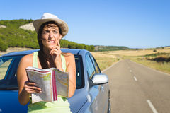 Lost woman on car roadtrip travel problem. Confused lost woman on car roadtrip travel problem searching in road map Royalty Free Stock Photography