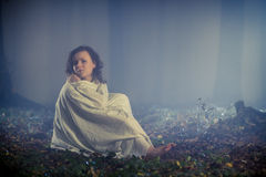 Lost woman with white sheet in dark forest. In autumn Stock Photography