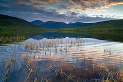 Lost World. Sunset on the mountain ridge Big Anngachag and mountain lake Royalty Free Stock Image