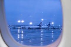 Lot airflight throw window at Warsaw airport, Poland. LOT airline throw window Warsaw airport flight transportation aviation aircraft fuselage stock photo