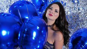 Lot of balloons in hands of joyful brunette near shiny wall close-up at festive event. Lot of blue balloons in hands of joyful brunette women near shiny wall stock video