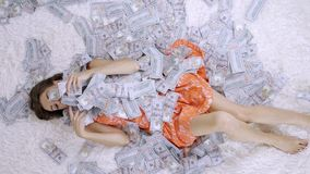 Lot of banknotes fly in the air on a girl lying on a white bed in slow motion. Huge wealth of money.  stock video
