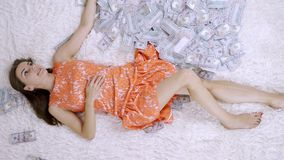Lot of banknotes fly in the air on a girl lying on a white bed in slow motion. Huge wealth of money.  stock footage