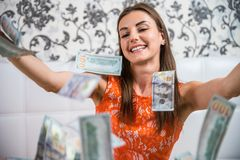 Lot of banknotes fly in the air on a girl lying on a white bed in slow motion. Huge wealth of money