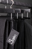 Lot of black pants jeans and jacket hanging on clothes rack.  background. sale sign.  friday. Close up. Royalty Free Stock Photography