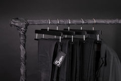 Lot of black pants jeans and jacket hanging on clothes rack.  background. sale sign.  friday. Close up. Royalty Free Stock Image