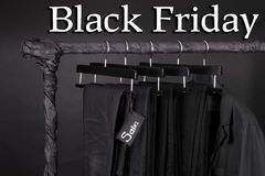 A lot of black pants jeans and jacket hanging on clothes rack.  background. sale sign.  friday. Close up. Stock Photo