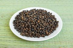 A lot of black pepper grains on a white saucer on a green table mat made of natural plant fibers. Natural food spices and royalty free stock images